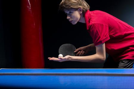 Portrait of young boy playing tennis on black background Reklamní fotografie