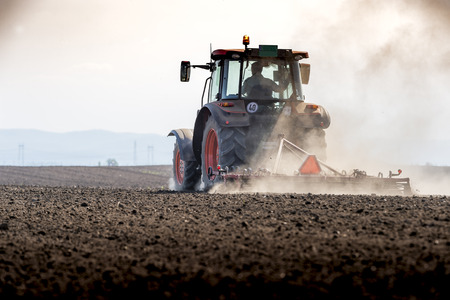 Tractor working in the field, preparing the land for planting,  working plowed field