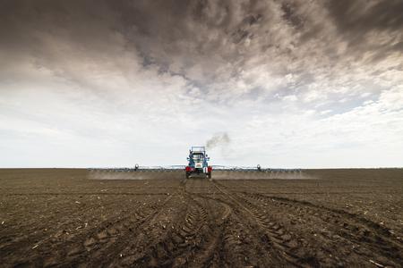 Tractor spraying soil  in springtime in field Reklamní fotografie