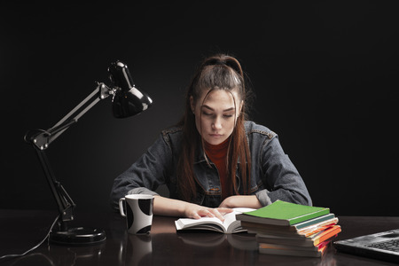 Female student, with books at her desk.  The girl is sitting at the table and study Banco de Imagens - 122299947