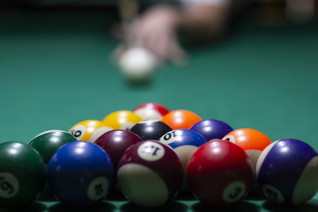 Billiard balls on green table with billiard cue. Snooker, pool game
