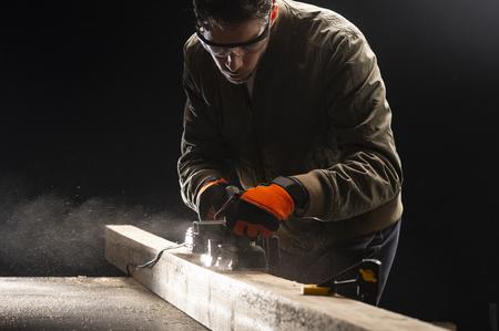 Carpenter works with electrical planer in workshop