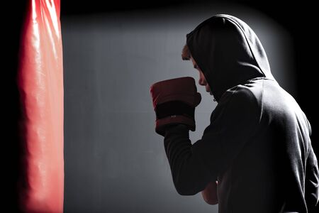 The young man workout a kick on the punching bag in gym