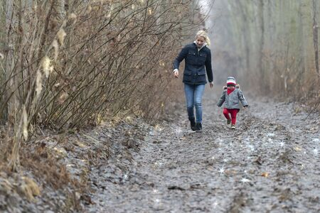 Mother with child walking by rural road in forest