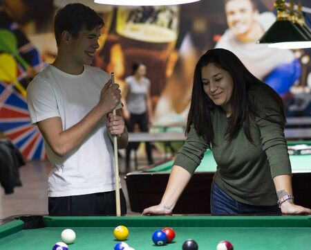 Young couple playing snooker together in bar Banco de Imagens
