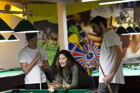 Group of young cheerful friends playing billiards