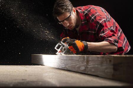 Le charpentier travaille avec le rabot électrique dans l'atelier