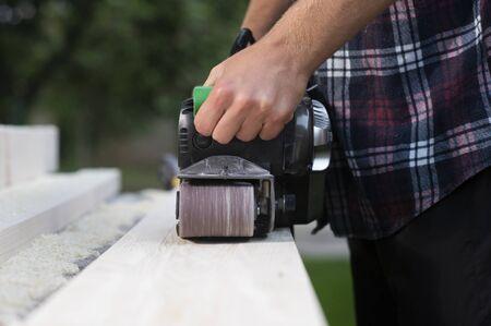Carpenter works with belt sander in carpentry outdoor Banque d'images - 135477069
