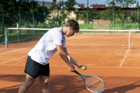A tennis player prepares to serve a tennis ball during a match. Tennis game background. Stock Photo - 135476980