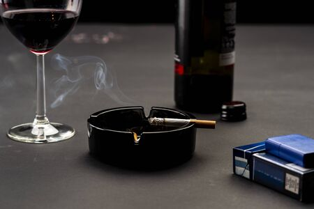 Cigarette, glass of wine and bottle of wine on black background