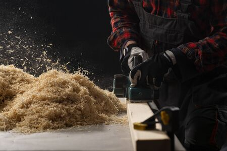 Carpenter works with electrical planer in workshop.Manufacture of wood products. Carpentry workshop
