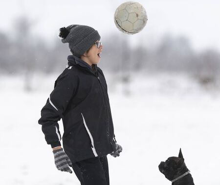 Young cute active boy with a football ball from out on winter field with snow on background. winter activities, soccer game Banco de Imagens