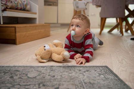 Cute little baby boy lying on hardwood and crawling over wooden parquet with pacifier in mouth