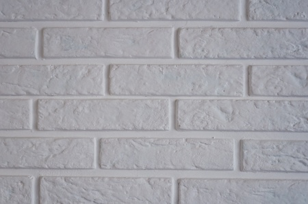 Part of a white brick wall in an interior photo