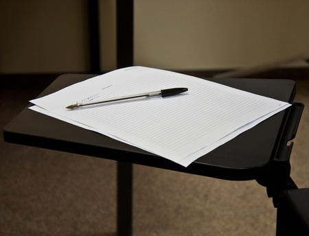 pen and a sheet of white paper on the folding table photo