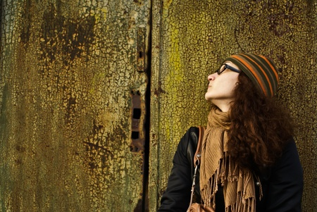 beautiful young adult woman in a cap and glasses  against a grungy rusty  wall Stock Photo - 8764786