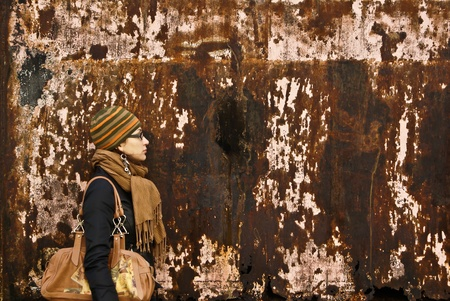 beautiful young adult woman in a cap and glasses  against a grungy rusty  wall Stock Photo - 8764787