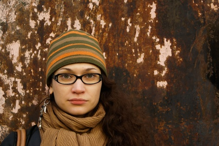beautiful young adult woman in a cap and glasses  against a grungy rusty  wall Stock Photo - 8764785