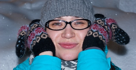 The happy girl in a cap and glasses clasps a head hands in gloves photo