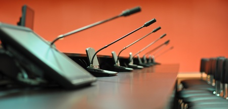 Conference table, microphones and office chairs close-up photo