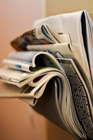 folded and crumpled newspapers and magazines in the wall bracket Standard-Bild