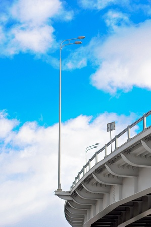 lamppost at the overpass on background of blue sky with clouds photo