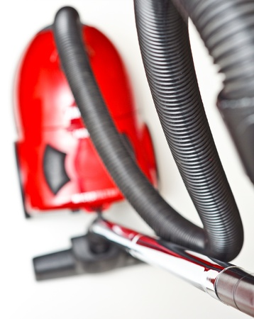 The red vacuum cleaner with a black hose on a white background Standard-Bild