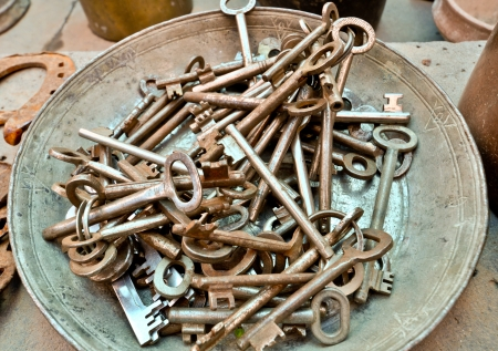 a lot of old brass key on an old plate photo