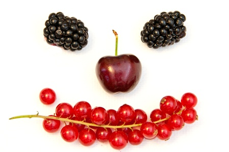 funny face from different berries on a white background