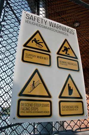 Danger warning signs hanging on a metal grid photo