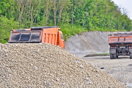 pile of gravel and dump trucks