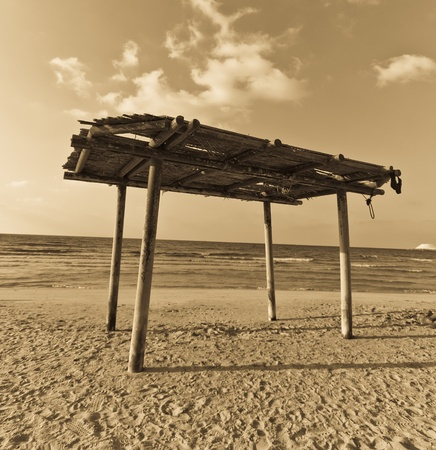 wooden canopy on the sandy beach and blue sky sephia tone photo