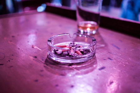 glass and an ashtray on the table photo
