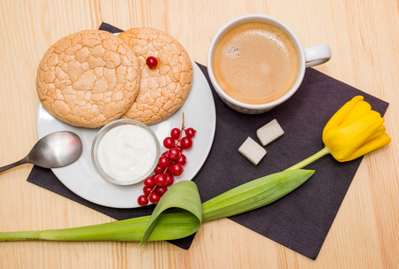 still life: a Cup of coffee and biscuits on plate on wooden table photo