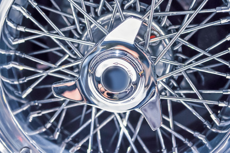 hubcap: central screw nut on classic car wire wheel Stock Photo