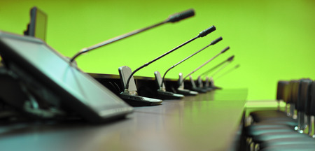 Conference table, microphones and office chairs, closeup, green photo