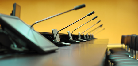 Conference table, microphones and office chairs, closeup, orange photo