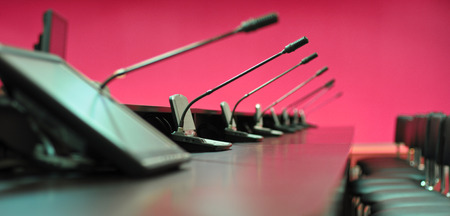 Conference table, microphones and office chairs, closeup, purple photo