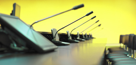 Conference table, microphones and office chairs, closeup, yellow photo