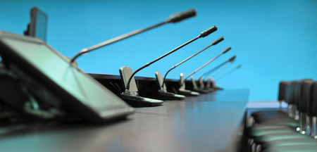 Conference table, microphones and office chairs, closeup, blue