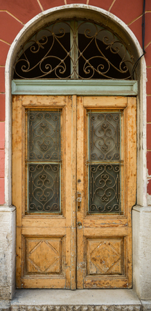rejas de hierro: antigua puerta de madera en mal estado irregular de color marrón con rejas de hierro forjado Foto de archivo