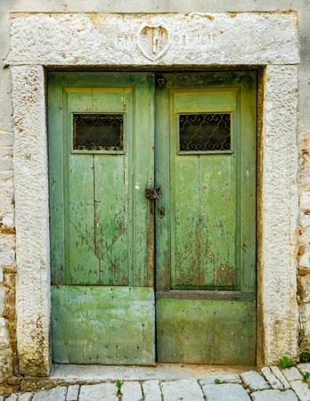 rejas de hierro: viejo verde irregular puerta de madera en mal estado, con barras de hierro forjado Foto de archivo