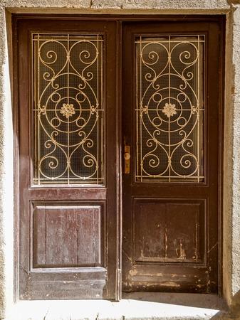 rejas de hierro: una antigua puerta de madera en mal estado desigual con barras de hierro forjado