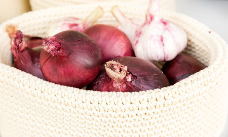 pealing: the red onions in a wicker basket close-up
