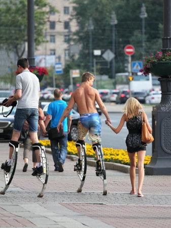 zancos: Los j�venes caminan por la calle en un zancos saltarines