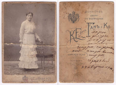 Tsarskoye Selo, Russia, August 24, 1916. An old photograph of a postcard (without restoration), which depicts a woman in an antique outfit. On the reverse side with a personalized printed text and coat of arms: