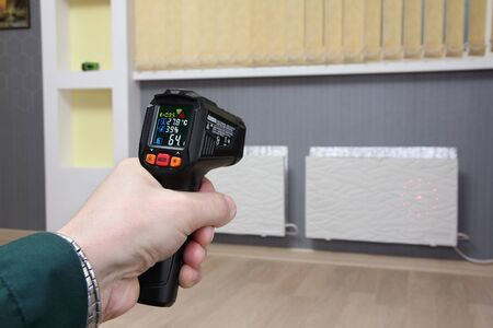 Infrared thermometer in hand measures the temperature of heating radiators in a room Stock Photo