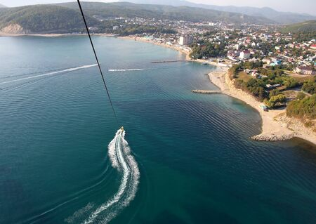 Parasailing above the water at a bird`s eye view. Coast of the city of Dzhubga on the Black Sea on a sunny day