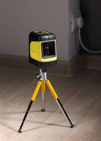 The construction laser level on a mini tripod stands on a laminate near the wall. The beam is visible on the instrument glass.