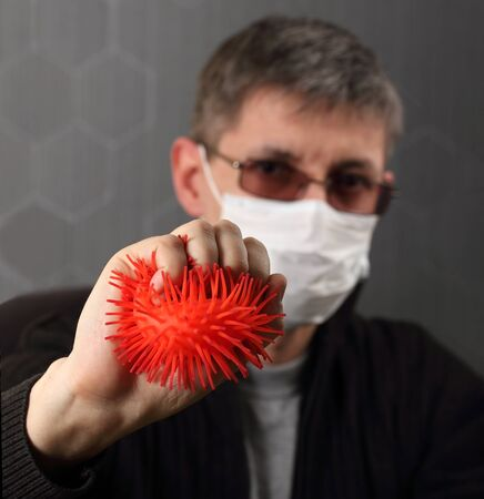 A man in a medical mask on his face fears the spread of the virus. Concept, man holds back the spread of infection